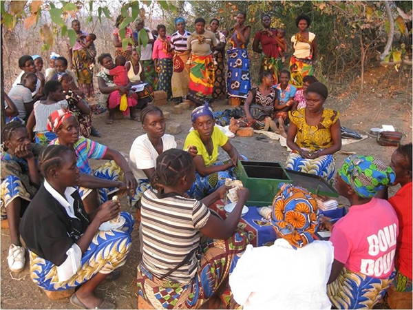A group of women in Zambia gathers to disperse loans from a communal savings.