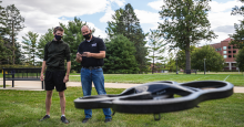 student and professor flying a drone