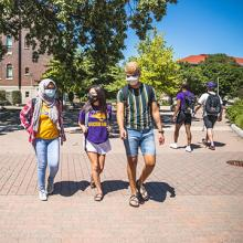 Masked UNI students walk on campus.