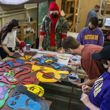 UNI art education students work on a piece of art they helped create with students from Holmes Junior High.